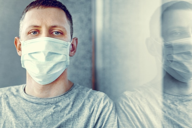 Coronavirus pandemia covid-19 e concetto di quarantena. uomo in una mascherina medica vicino alla finestra. Foto Premium