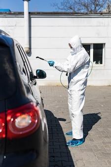 Pandemia di coronavirus. il disinfettante in tuta protettiva e maschera spruzza disinfettanti per auto all'aperto