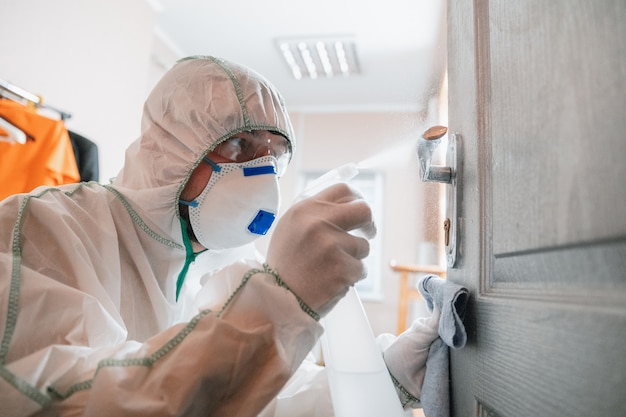 Pandemia di coronavirus. un disinfettante in una tuta protettiva e una maschera spruzza disinfettanti in casa o in ufficio. protezione contro la malattia covid-19. prevenzione della diffusione del virus della polmonite con le superfici.