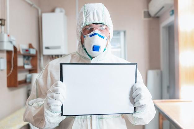 Pandemia di coronavirus un disinfettante in tuta protettiva e maschera spruzza disinfettanti