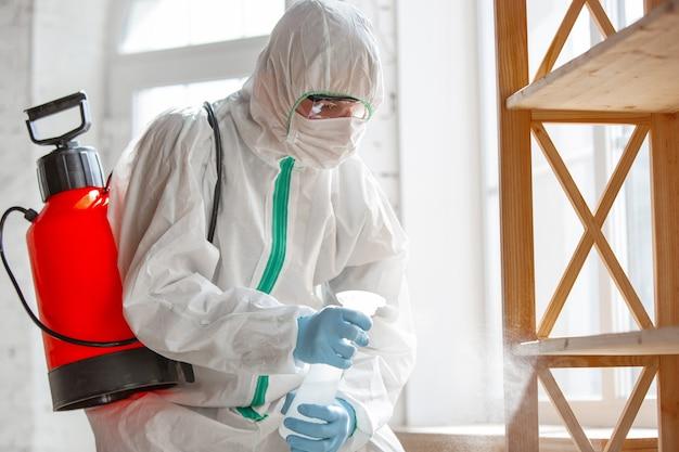 Pandemia di coronavirus un disinfettante in una tuta protettiva e spray per maschere