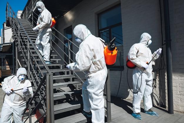 Pandemia di coronavirus. un disinfettante in una tuta protettiva e una maschera spray disinfettanti in casa o in ufficio. protezione contro la malattia covid-19. prevenzione della diffusione del virus della polmonite con le superfici.
