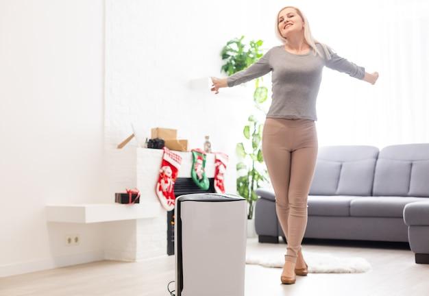 Panico da coronavirus, purificatore d'aria in un soggiorno, aria di umidificazione in appartamento durante il periodo di autoisolamento a causa della pandemia di coronavirus