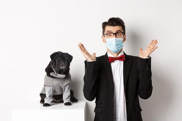 Coronavirus, animali domestici e concetto di celebrazione. giovane stupito in maschera e vestito che fissa la telecamera sorpreso, simpatico cane nero seduto vicino al proprietario in abito da festa, bianco.