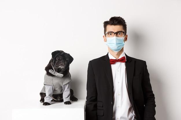 Coronavirus, animali domestici e concetto di celebrazione. bel giovane uomo e cane che indossa abiti, ragazzo ha maschera medica, in piedi su bianco.