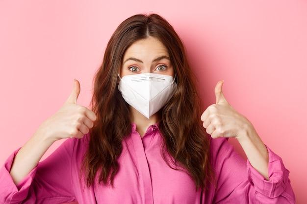 Coronavirus, misure preventive e concetto di salute. felice bella signora in respiratore medico da covid-19, mostra il pollice in alto in segno di approvazione, elogia la buona scelta, muro rosa. copia spazio