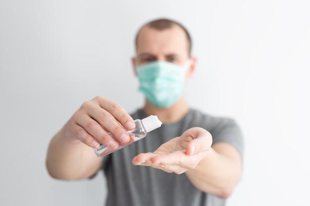 Protezione da coronavirus, igiene delle mani e concetto di disinfezione - primo piano dell'uomo in maschera medica che pulisce le mani con gel igienizzante
