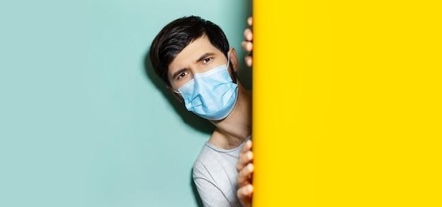 Prevenzione della quarantena del coronavirus. ritratto in studio di giovane ragazzo con maschera facciale medica, esce tra due sfondo di colori giallo e acqua.