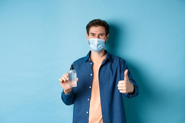 Coronavirus, quarantena e concetto di allontanamento sociale. modello maschio felice in maschera facciale che mostra disinfettante per le mani e pollice in alto, lodare il buon prodotto, sfondo blu.