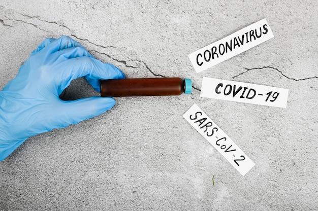 Rimozione del coronavirus tramite biopsia. il medico esegue un esame del sangue biochimico per rilevare il coronavirus. avvicinamento. su uno sfondo nero. il concetto di coronavirus.