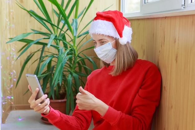 Coronavirus e autoisolamento natalizio. una donna in cappelli rossi della santa e mascherina medica congratulandosi con la famiglia o gli amici con un telefono.