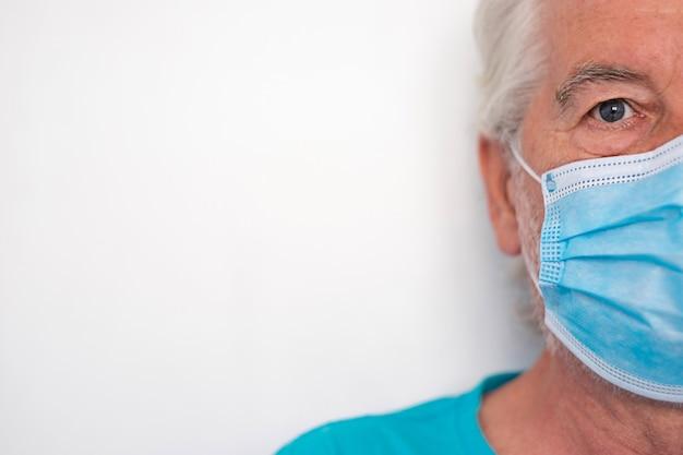 Coronavirus. uomo anziano su sfondo bianco che indossa una maschera protettiva per evitare l'infezione da coronavirus. primo piano sul viso con gli occhi azzurri, copia spazio