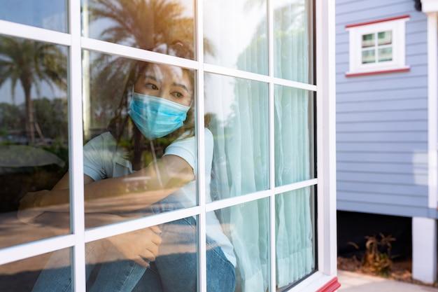 Coronavirus. donna malata di virus corona guardando attraverso la finestra e indossando maschera di protezione e recupero dalla malattia in casa. quarantena. paziente isolato per prevenire l'infezione nuova normalità.