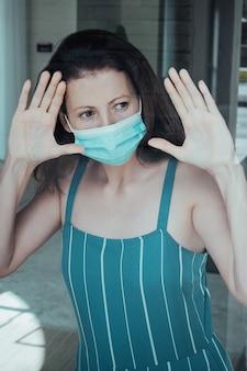 Coronavirus. donna malata di corona virus che guarda attraverso la finestra e indossa una maschera di protezione