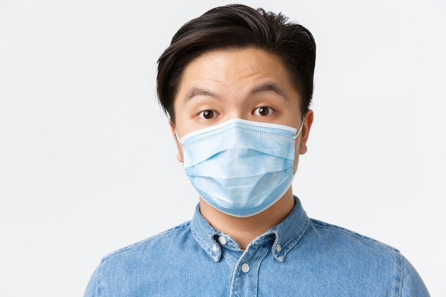 Coronavirus, distanza sociale e concetto di stile di vita. uomo asiatico sorpreso in maschera medica che alza le sopracciglia in soggezione, in piedi stupito su sfondo bianco, usando misure protettive durante il covid-19.