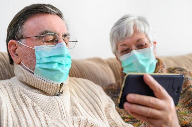 Coronavirus. resta a casa, stile di vita. coppie anziane allegre che si siedono su un sofà su una quarantena a casa, facendo una videochiamata con lo smartphone. coppia senior indossando maschere protettive.