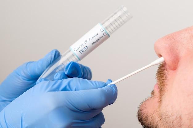 Test di coronavirus operatore medico o infermiere che preleva un tampone nasale per il campione di coronavirus dal paziente