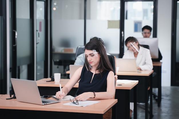 Coronavirus: donna d'affari che lavora nello spazio di co-working seguendo le distanze sociali e le nuove politiche normali