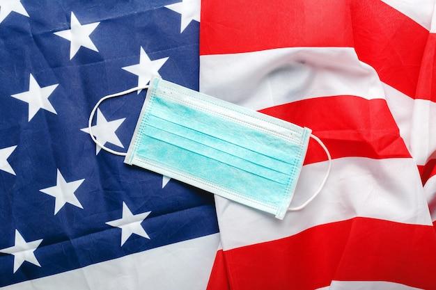 Coronavirus negli usa. mascherina chirurgica protettiva sulla bandiera nazionale americana.
