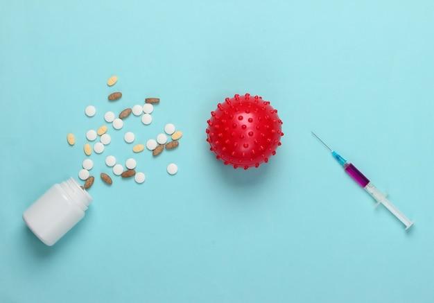 Vaccino e trattamento contro il coronavirus. ceppo di virus, siringa e pillole sull'azzurro.