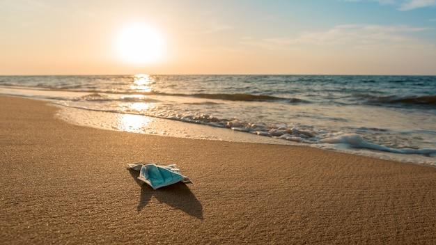 Rifiuti coronavirus che inquinano l'ambiente in spiaggia. maschere usa e getta scoppio spazzatura nell'oceano. maschera medica usa e getta usata scartata nelle acque marine della spagna