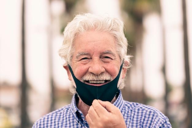 Coronavirus. l'uomo anziano dai capelli bianchi si toglie la maschera protettiva per sorridere alla telecamera.
