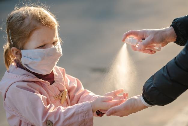 Coronavirus. prodotto disinfettante dello spruzzo di uso della donna sul bambino delle mani in una maschera protettiva sulla via. misure preventive contro l'infezione da covid-19. spray antibatterico per il lavaggio delle mani. protezione delle malattie.