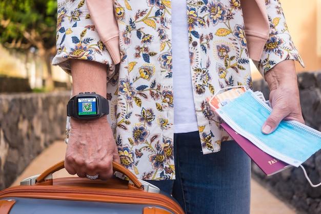 Coronavirus.donna con bagagli e documenti per il viaggio, indossa un orologio da polso con certificato digitale di vaccinazione contro covid-19