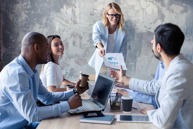 Squadra aziendale e manager in una riunione. il leader distribuisce i documenti ai colleghi.