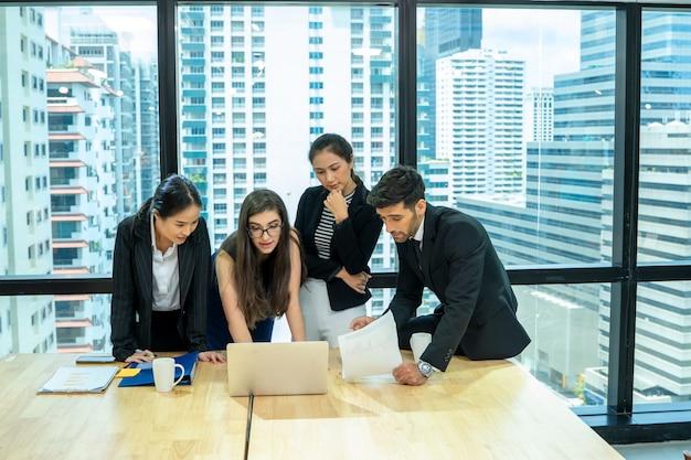 Team aziendale aziendale e manager che si incontrano e lavorano insieme in un ufficio moderno, piena concentrazione sul lavoro.