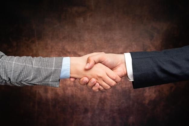 Gli uomini d'affari aziendali stretta di mano all'interno. due persone professionalmente ben vestite gesticolando insieme. collega di lavoro partner firmare l'accordo per il contratto