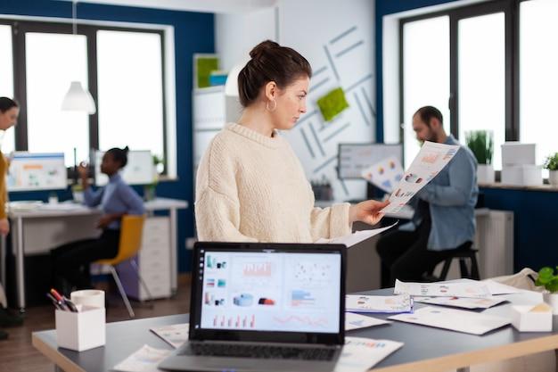 Imprenditrice aziendale leggendo le statistiche nell'ufficio della società di avvio. statistiche internet online di imprenditore professionale aziendale di successo. imprenditore esecutivo, manager leader che lavora in piedi