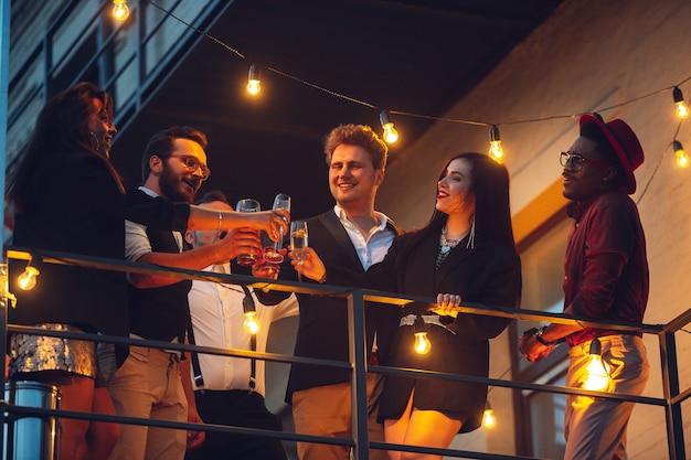 Celebrazione aziendale nella calda luce delle lampade nella sera d'estate, giovani amici, colleghi sembrano felici, parlano, si divertono. vacanze, fine settimana, affari e finanza, concetto di amicizia. costruzione di squadra.