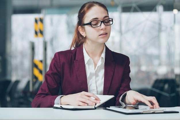 Ritratto di dipendente aziendale. pianificazione del lavoro. giovane donna attraente con gli occhiali che controlla tablet mentre prende appunti nel pianificatore di giorno.