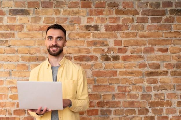 Impiegato aziendale in posa con un computer portatile