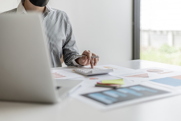 Un finanziere aziendale sta controllando i documenti finanziari per la correttezza dei rendiconti finanziari, sta controllando i numeri sui documenti utilizzando una calcolatrice per calcolare. concetto di finanza.