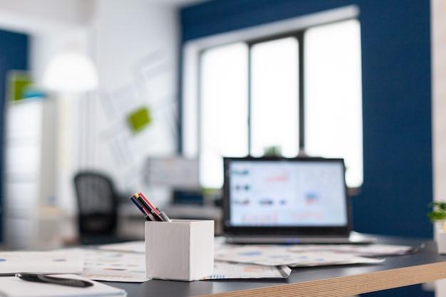 Ufficio moderno aziendale con laptop sulla scrivania che mostra grafici finanziari. area di brainstorming nel centro commerciale senza nessuno, colpo di stanza vuota con mobili moderni e parete blu.