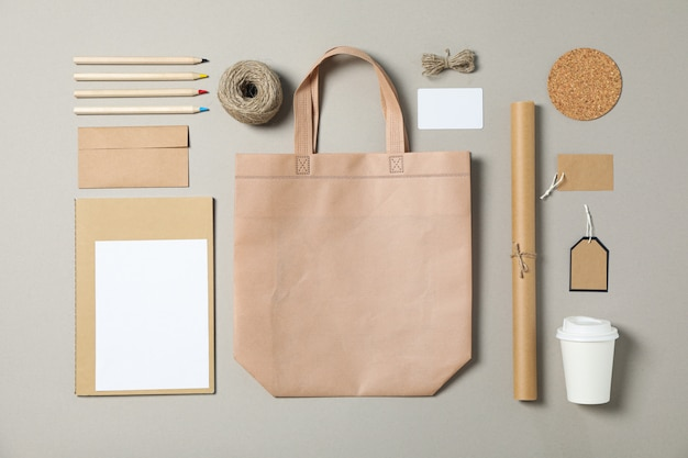 Cancelleria corporativa, tote bag e tazza di carta su sfondo grigio.