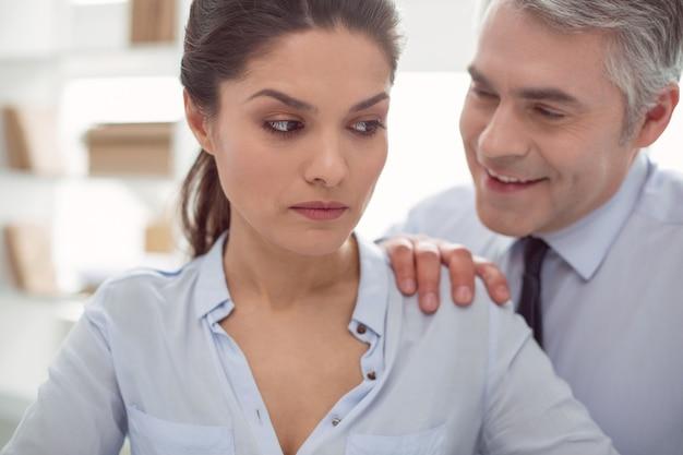 Subordinazione aziendale. bella donna lunatica e infelice seduta al tavolo e ascolta il suo capo mentre viene molestata sessualmente da lui