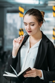 Ritratto dell'impiegato corporativo della donna. la pianificazione aziendale conta. stagista sorridente con pianificatore di giorno nell'area di lavoro dell'ufficio.