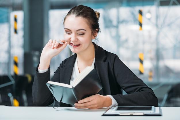 Ritratto dell'impiegato corporativo della donna. la pianificazione aziendale conta. stagista sorridente con pianificatore di giorno sul posto di lavoro.