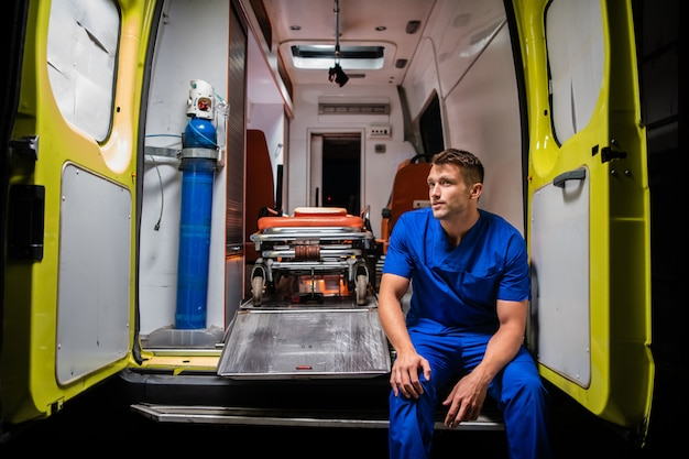 Corpsman in uniforme blu seduto in un pensiero auto ambulanza