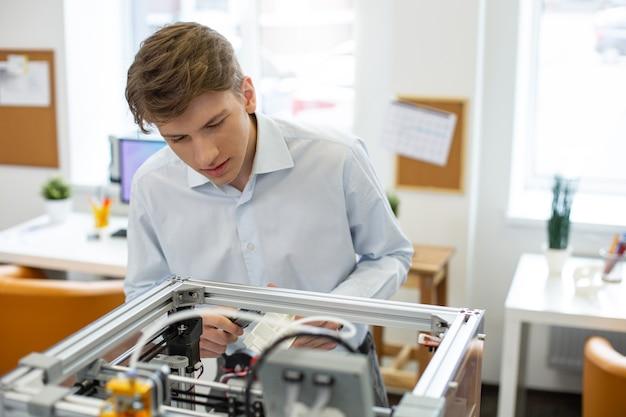 Correggere i dati. affascinante giovane che scopre i parametri di un modello realizzato con una stampante 3d mentre utilizza un calibro digitale