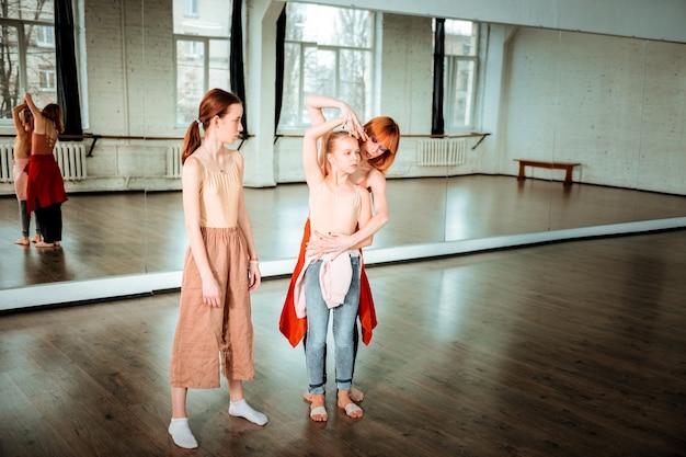 Posizione corretta. insegnante di danza sottile dai capelli rossi che mostra la posizione del braccio al suo studente mentre trascorre il tempo in studio di danza