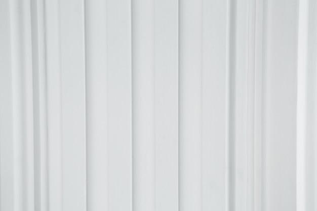Una recinzione ondulata di lamiere grigie con vite