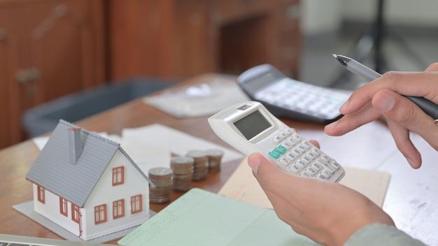 Cose-up shot di mano utilizzando la calcolatrice per le spese domestiche.