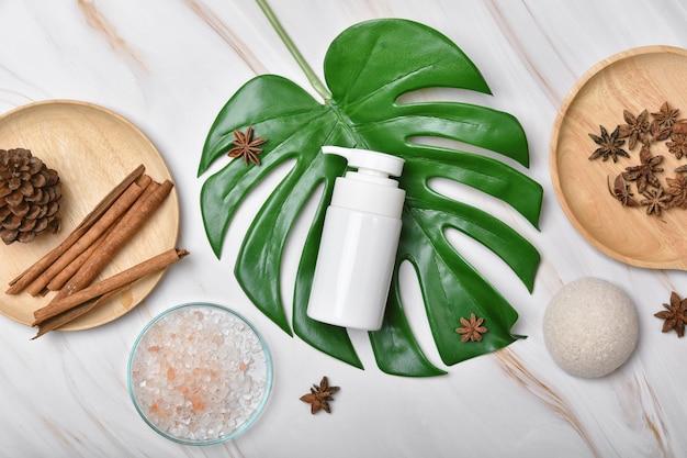 Contenitori per bottiglie cosmetiche che imballano con foglie di erbe verdi, etichetta vuota per mock-up del marchio biologico