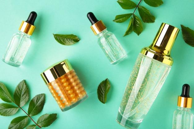 Contenitori per bottiglie cosmetiche con foglie verdi sulla superficie della menta