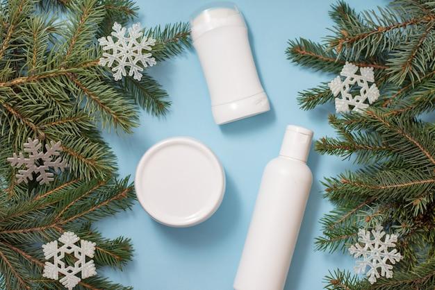 Flaconi e barattoli per la cosmetica sull'azzurro con cornice di rami di albero di natale e fiocchi di neve giocattolo.