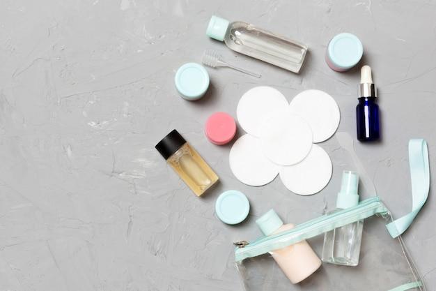 Bottiglie e barattoli cosmetici su un fondo concreto